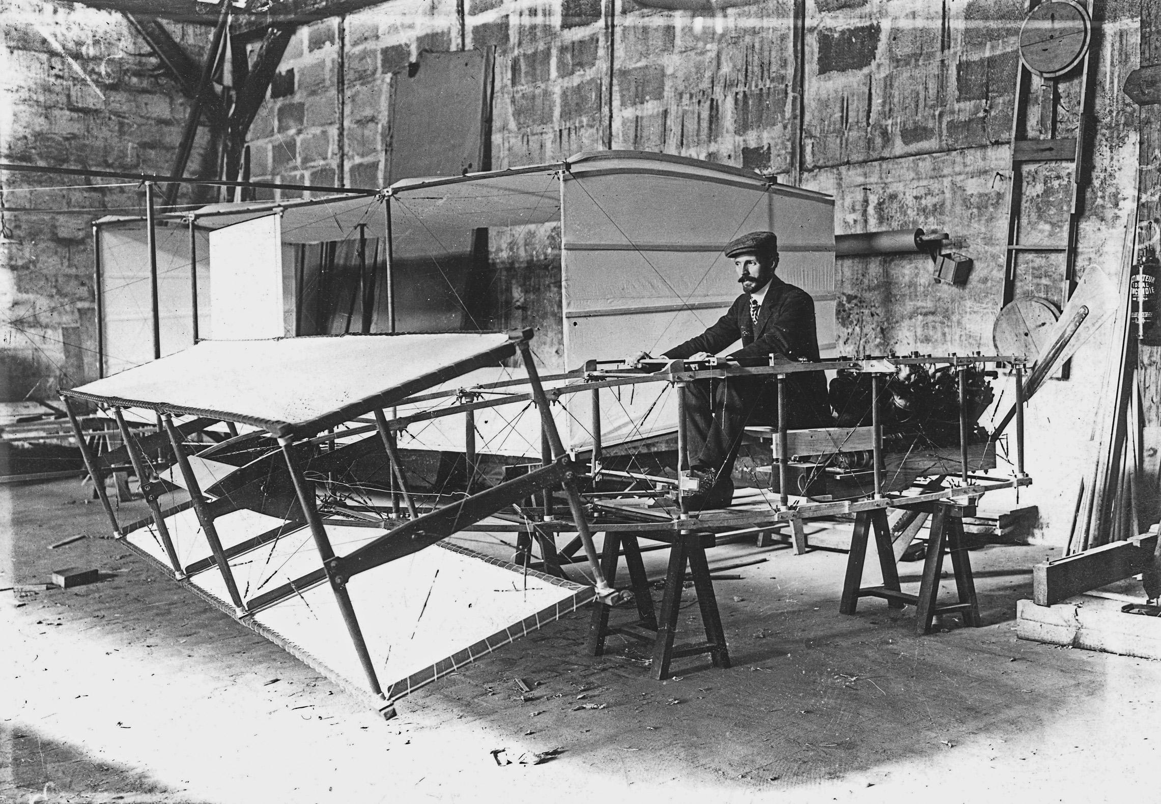 Henry Farman, dans l'atelier de la rue de la ferme essaye les commandes de son avion. Archives municipales de Boulogne-Billancourt